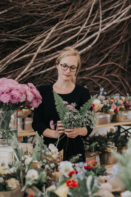 Hannah Ross Clarke examines a floral arrangement of fresh cut flowers at the Wylde Flowers studio in Raleigh, N.C.