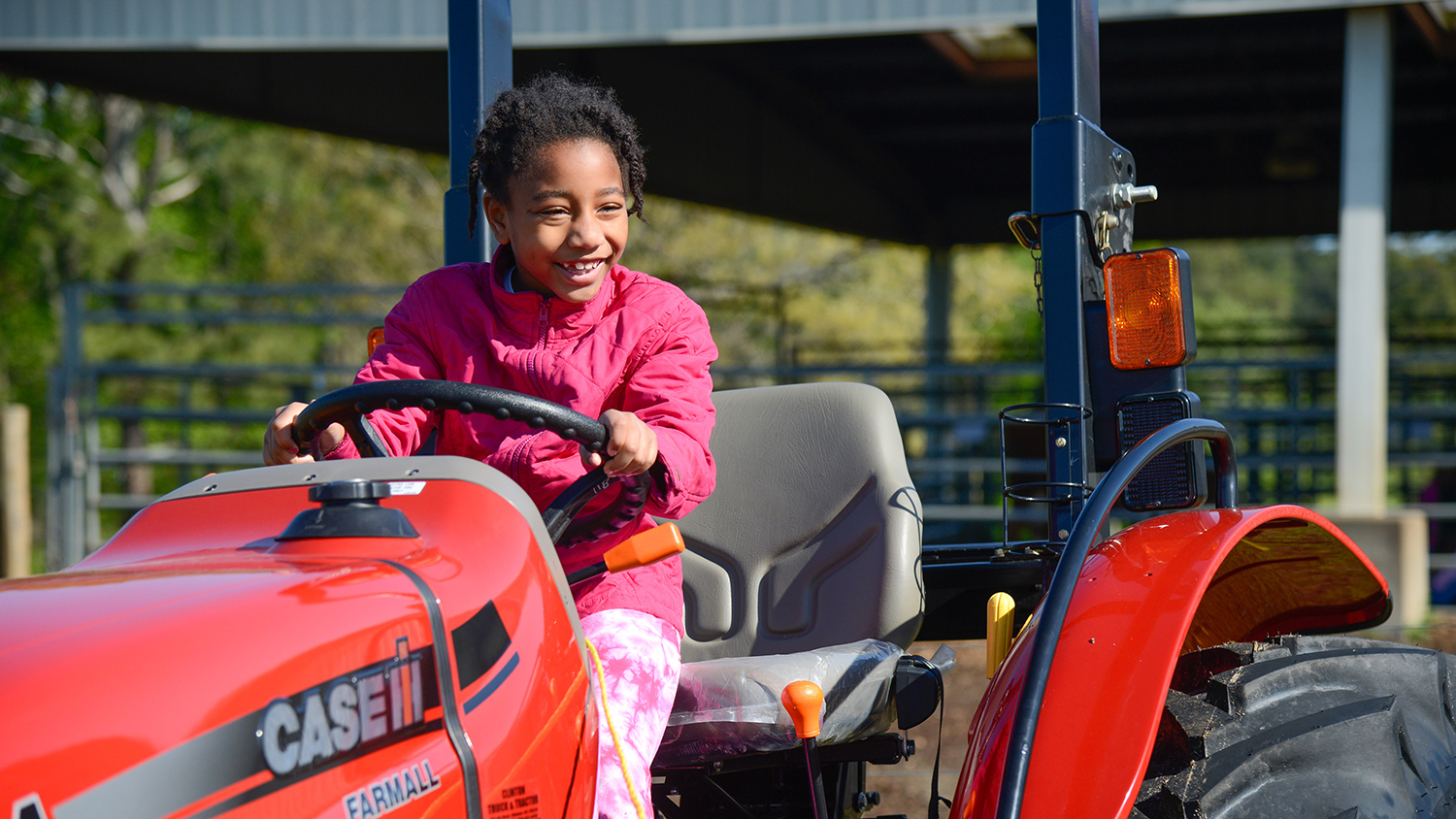 Child driving red tractor