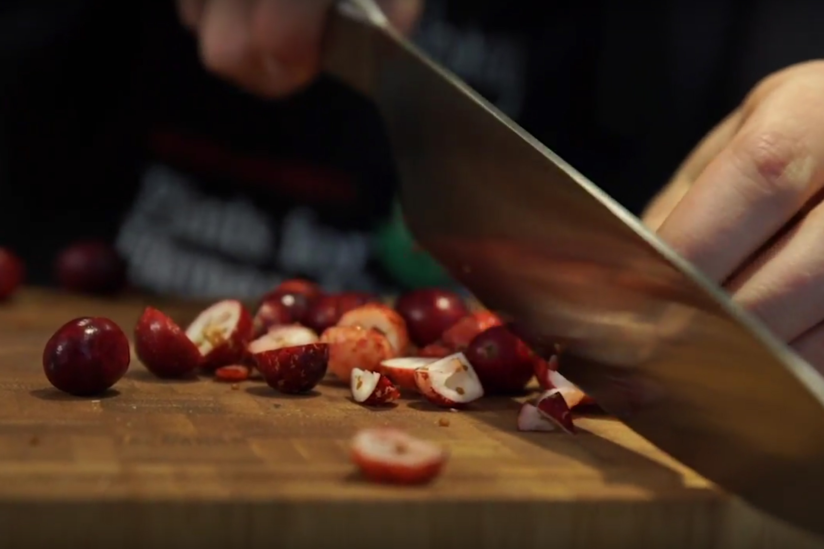Knife cutting cranberries on a wooden cutting board
