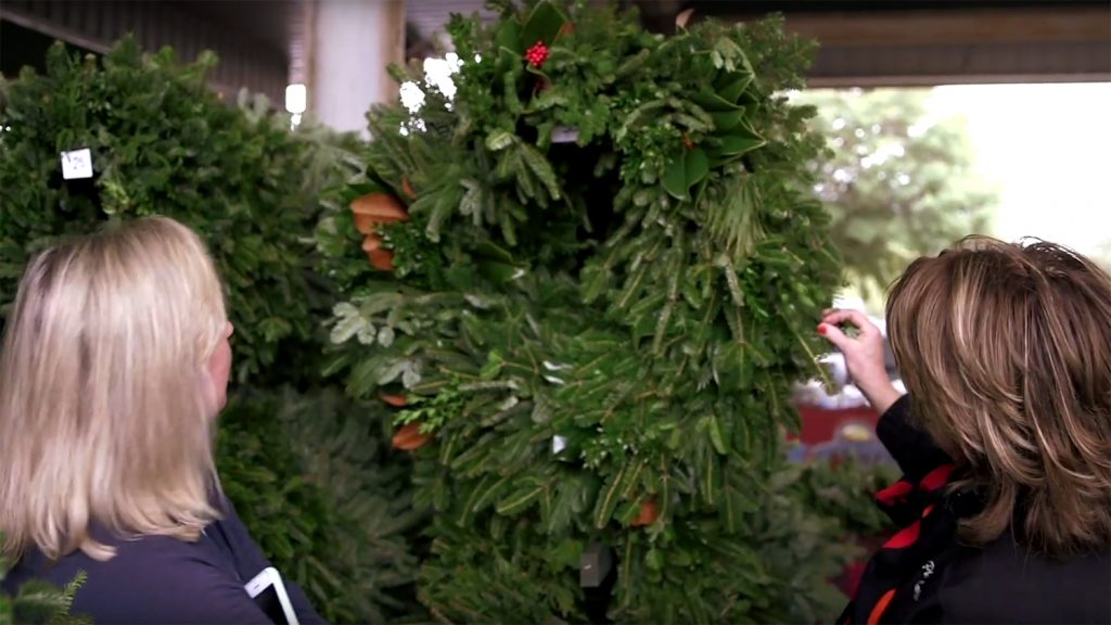 Two women looking at a green holiday wreath hanging on a rack.
