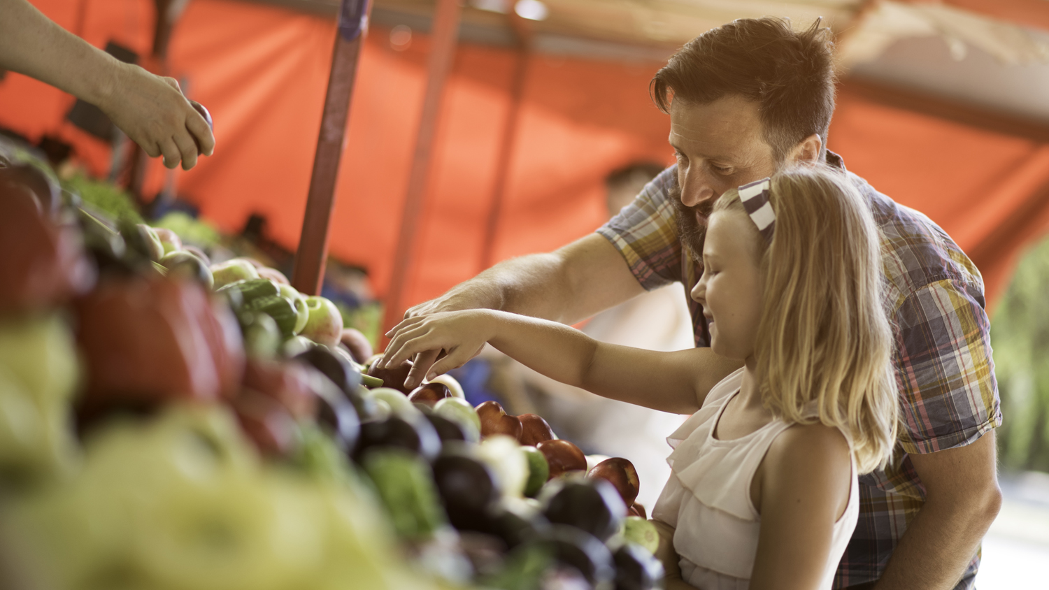 Smiling bearded man and his daughter buying fresh produce at outdoor farmers market stand.