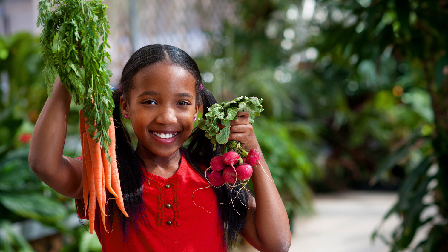 Girl holding carrots and radishes while standing in a garden.