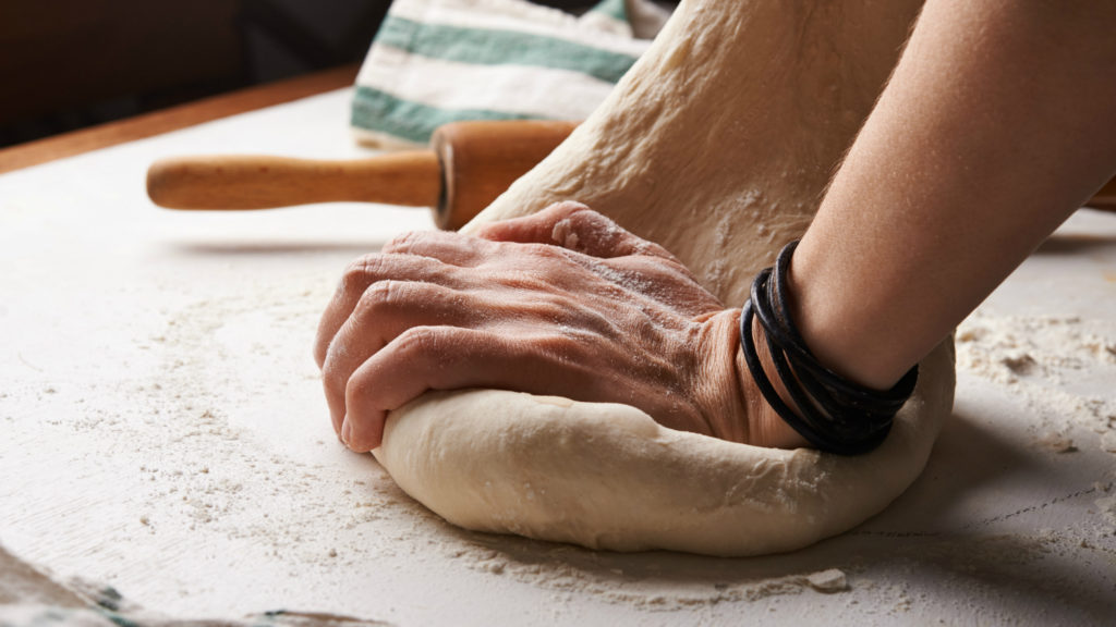 A photo of hands kneading bread