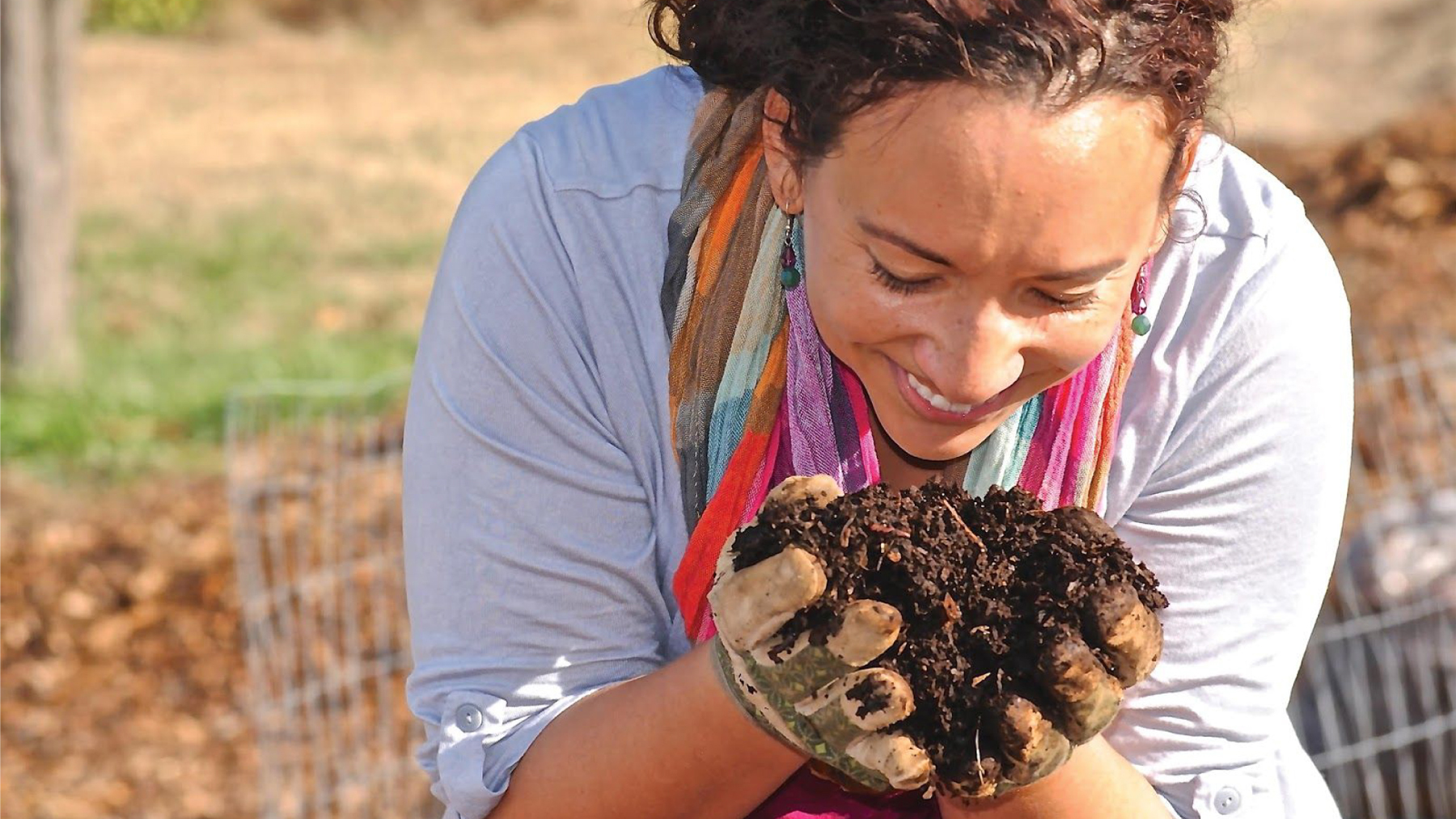 A smiling woman examines soil up close in her hands while gardening.