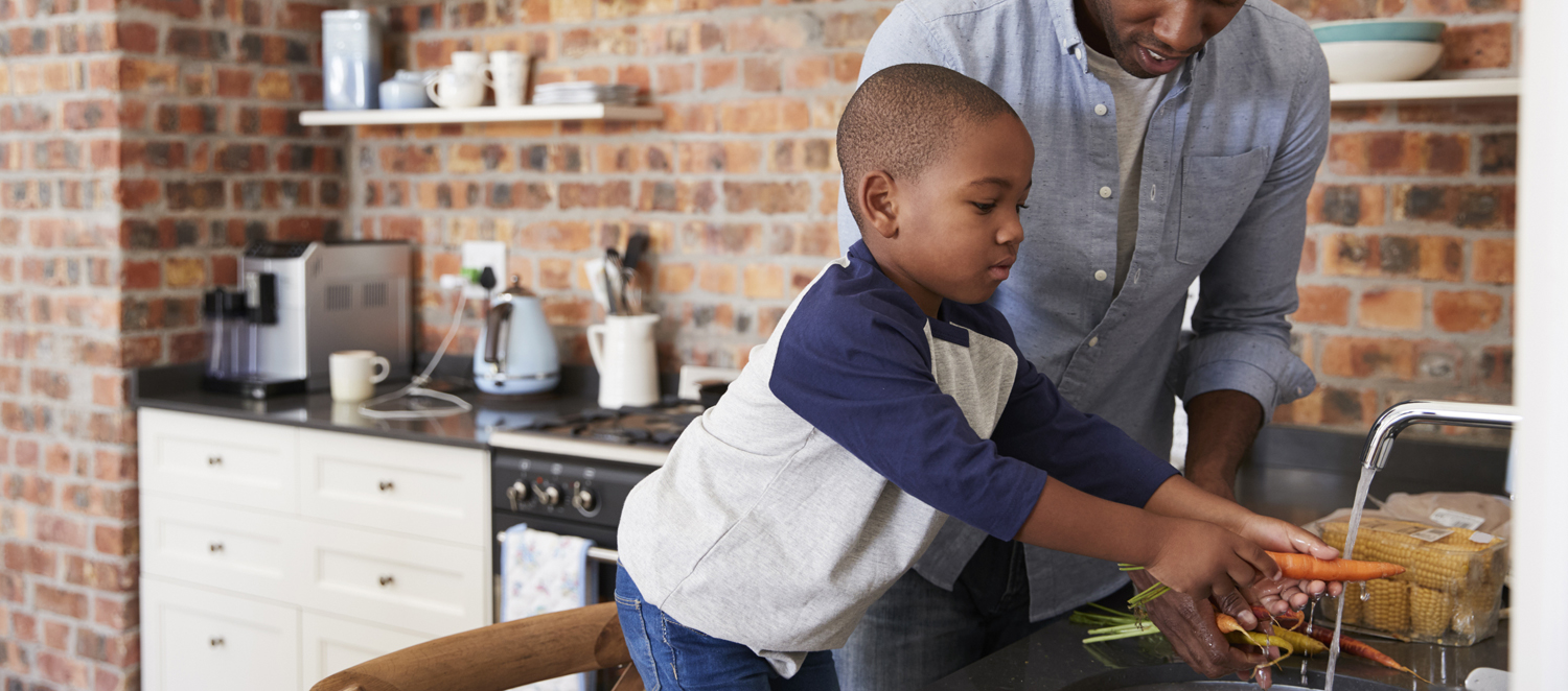 Young boy helping his father wash carrots under running water in kitchen sink
