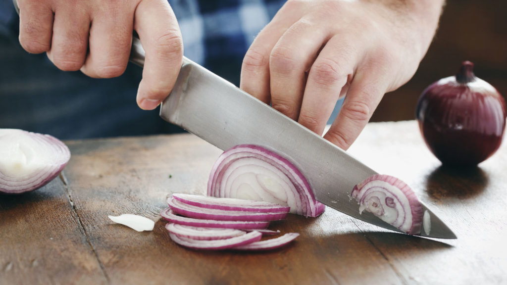 Male hands chopped red onion with a chef's knife on wooden table close up