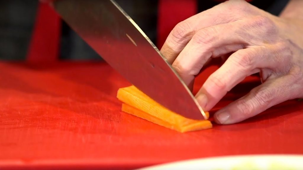 Close up of a hand holding a chef's knife and cutting a carrot