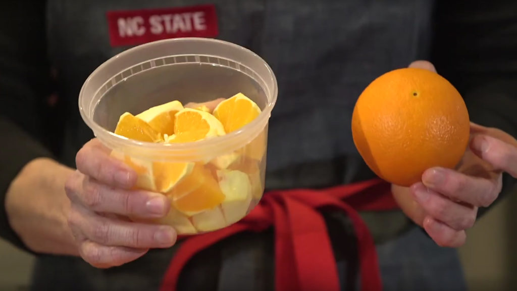 Close up of hands holding an unpeeled orange and a cup of peeled orange slices