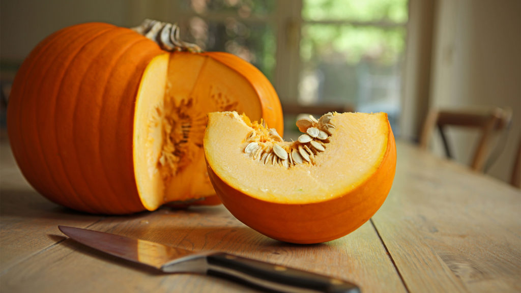 An orange pumpkin on a kitchen table with a slice cut off and laying next to the pumpkin, as is a kitchen knife.