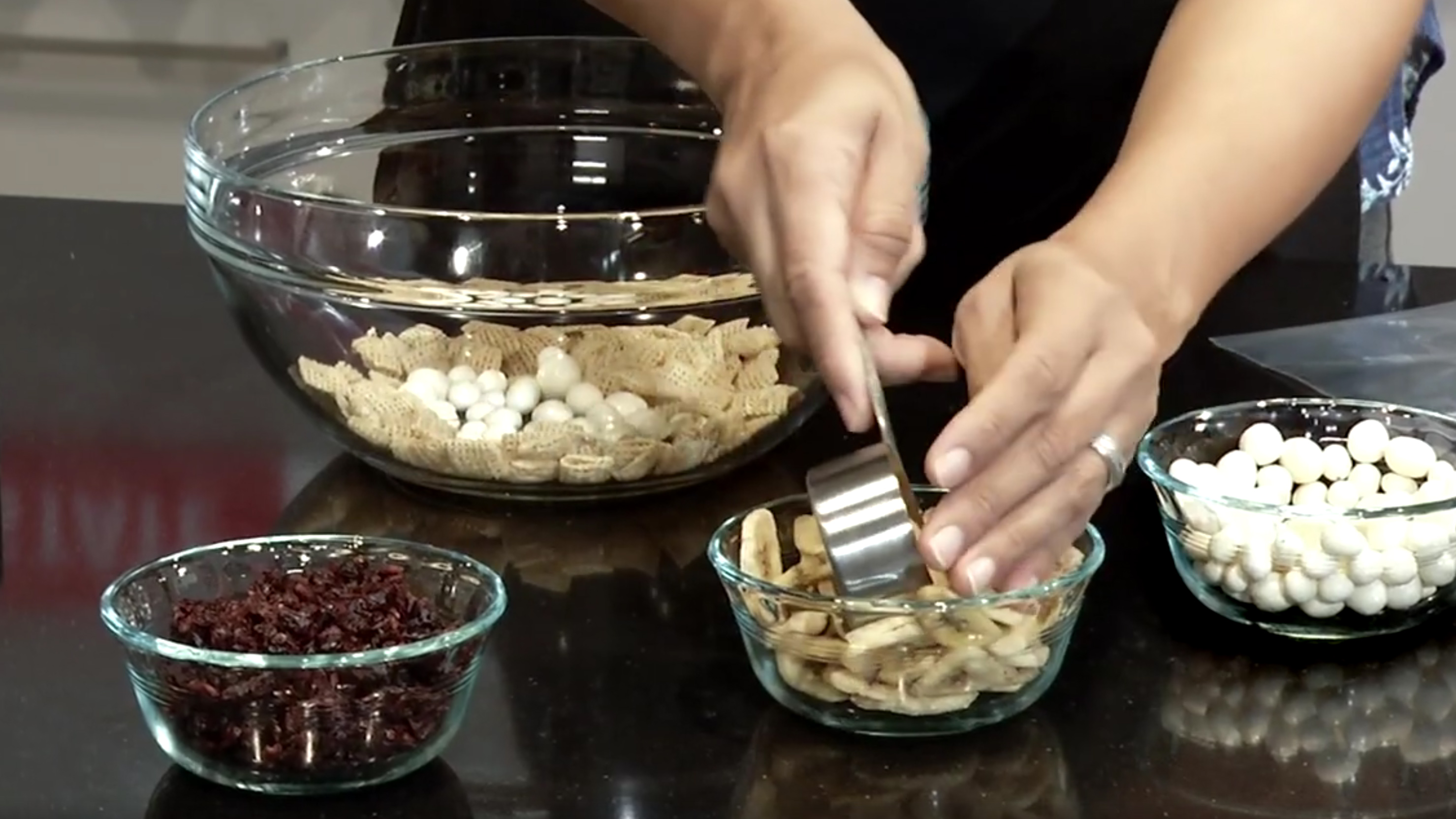 Close up of hands scooping out dried bananas, alongside glass bowls of other healthy snacks like raisins, to make a toss up snack bag.