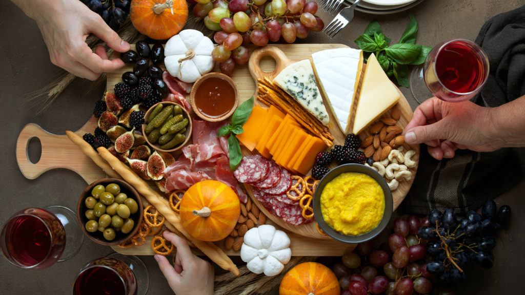 Overhead view of fall holidays table with friends hands picking some fingerfood appetizers from a charcuterie board