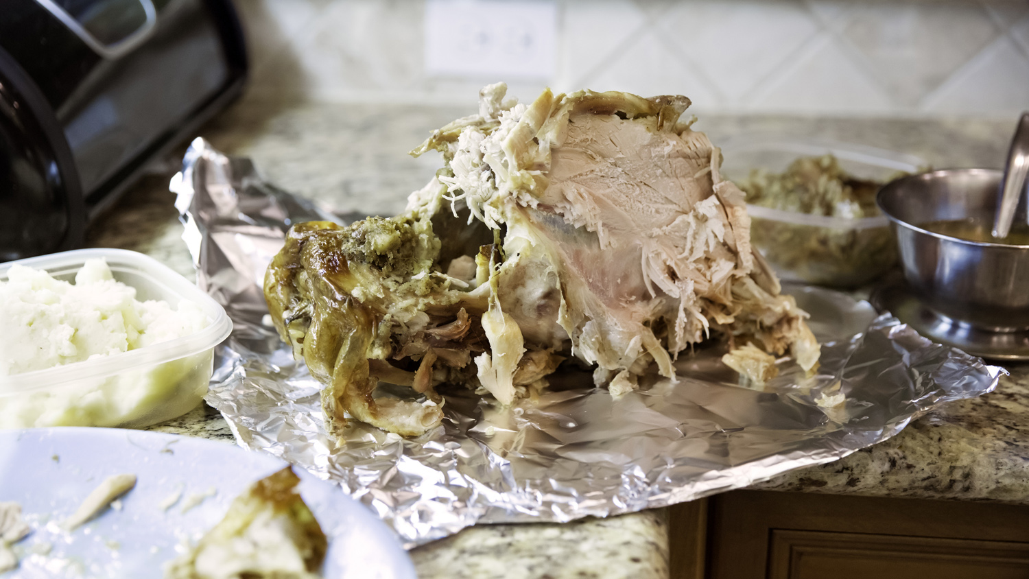 Leftover sliced turkey on a sheet of aluminum foil on the kitchen counter after a big holiday dinner.