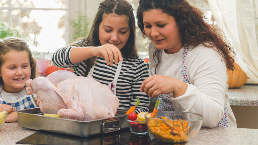 Mother and her daughters preparing stuffed turkey with side dishes for Thanksgiving