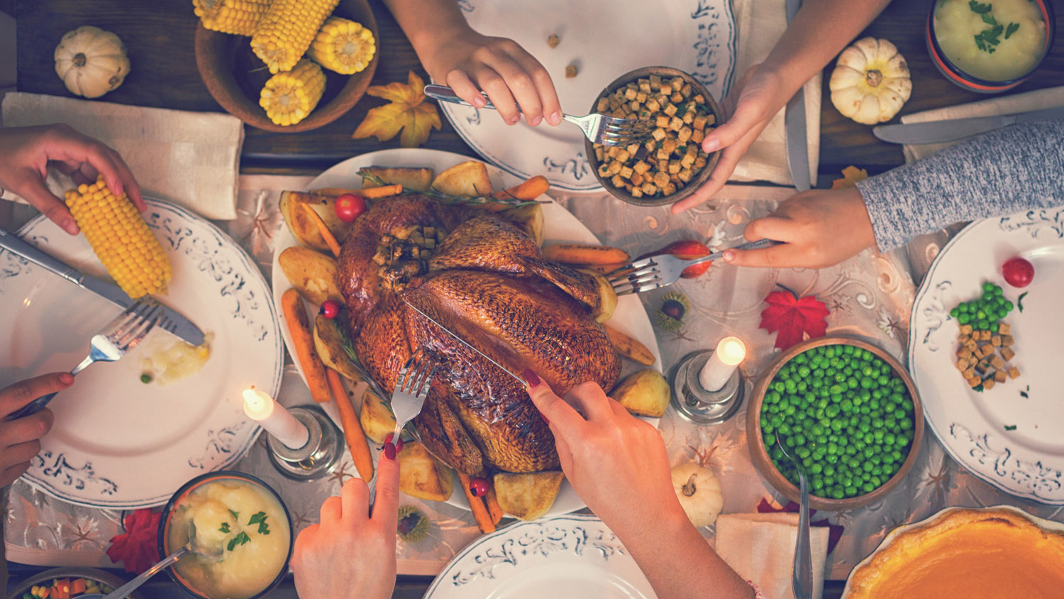 Overhead view of a family celebrating Thanksgiving at the dinner table with a traditional roasted turkey with side dishes