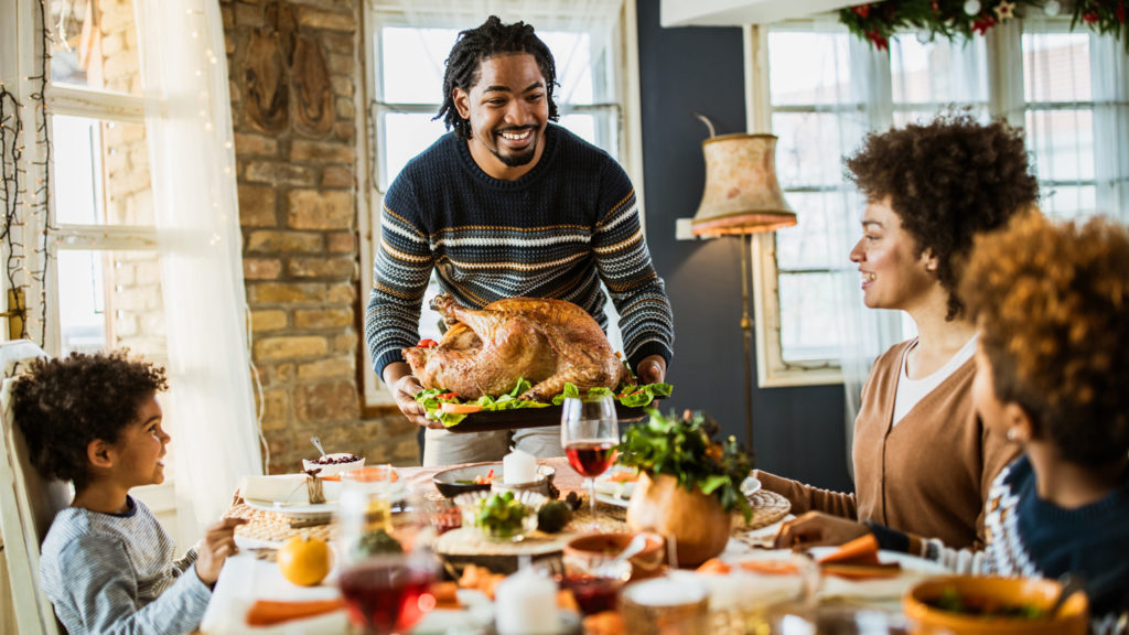 Happy father bringing Thanksgiving turkey to the table for his family's' meal.