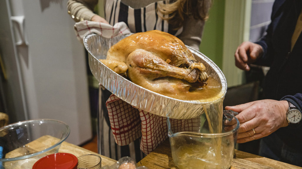 A close-up shot of a woman draining the stock from a roast turkey.