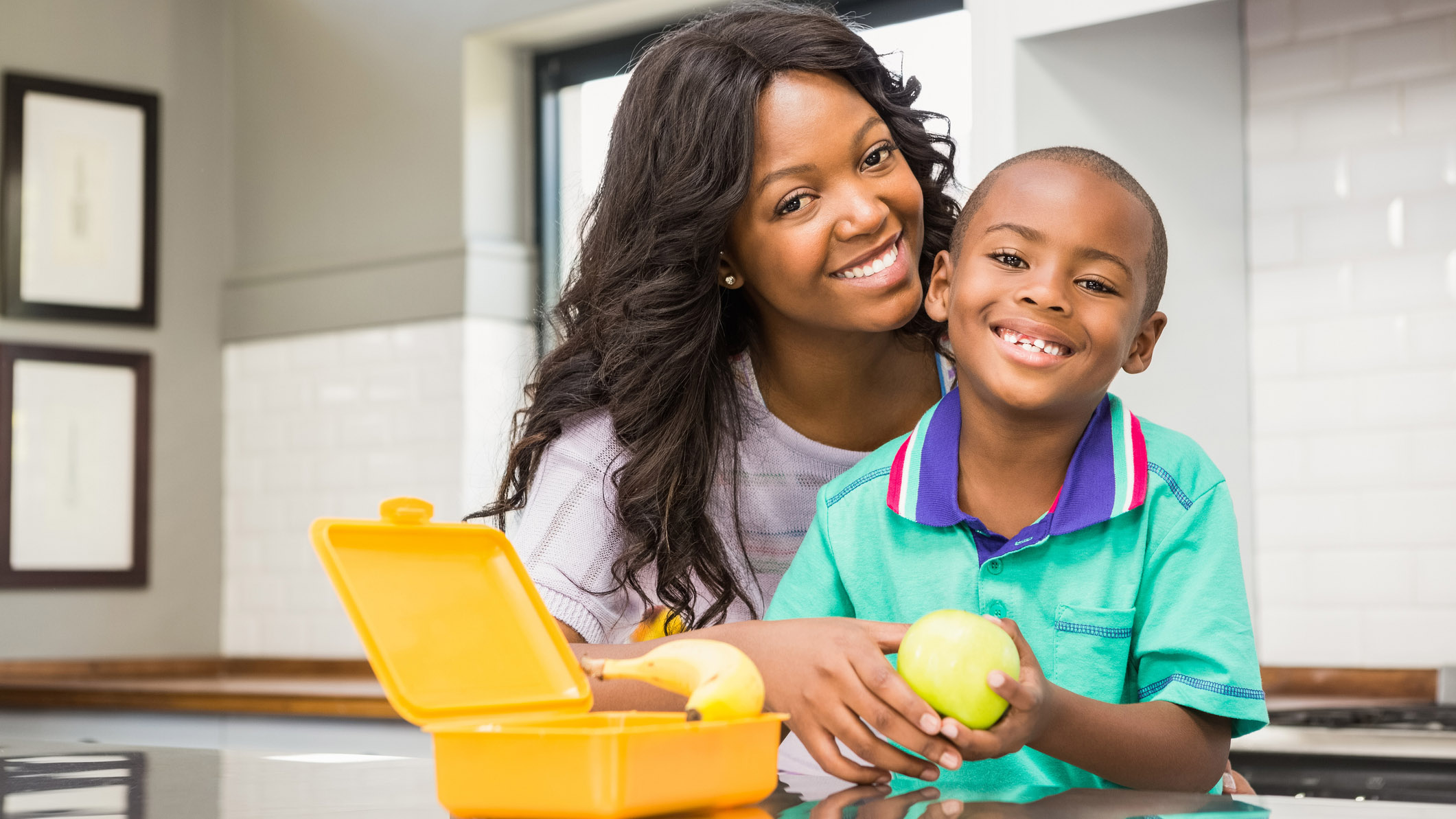 Smiling mnother and her young son at the kitchen counter with a yellow lunchbox and apple in front of them