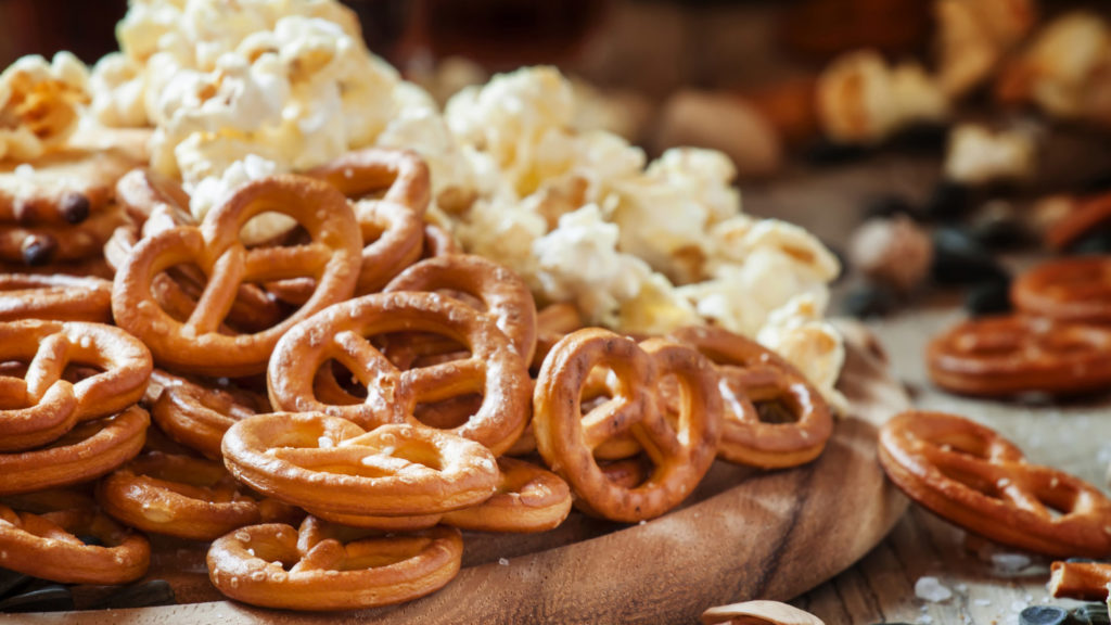A wooden cutting board with pretzels and popcorn