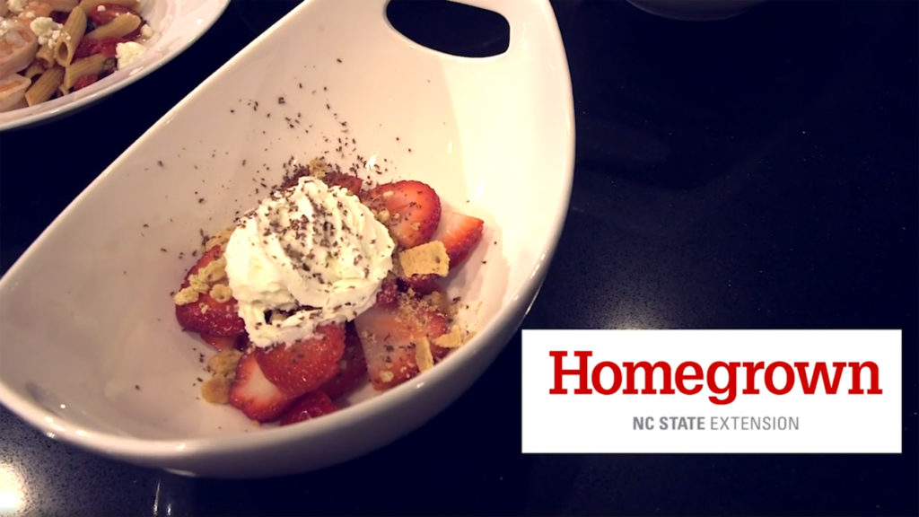 A Grand Marnier strawberry parfait is displayed in a white dish on a black counter with the Homegrown by NC State Extension logo beside it