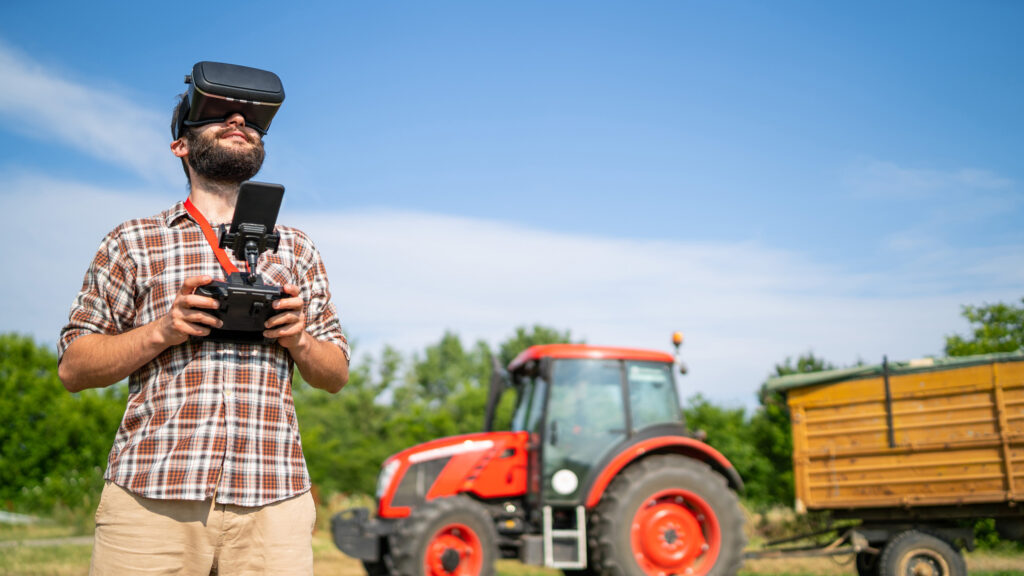 Farmer flying a drone over a field using a VR headset