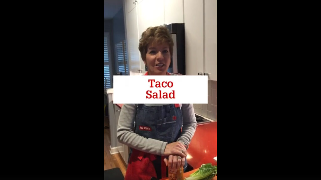 "A woman wearing an apron is smiling while standing at her kitchen counter with ingredients for a taco salad laid out. The words ""Taco Salad"" are displayed across the image."