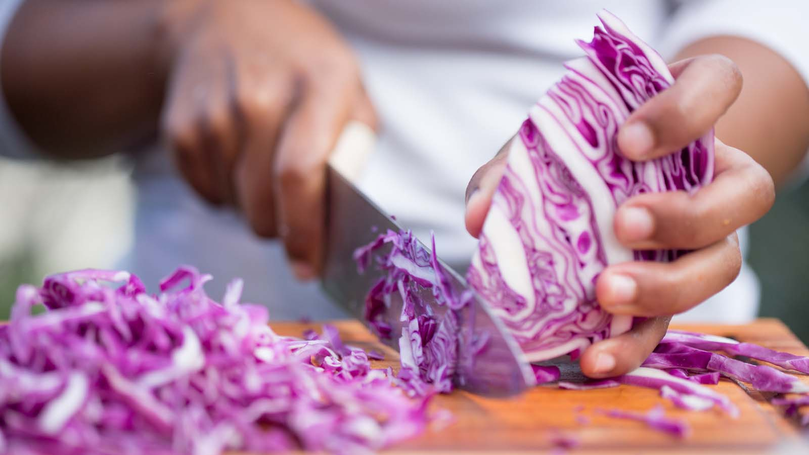 A person chops a head of red cabbage.