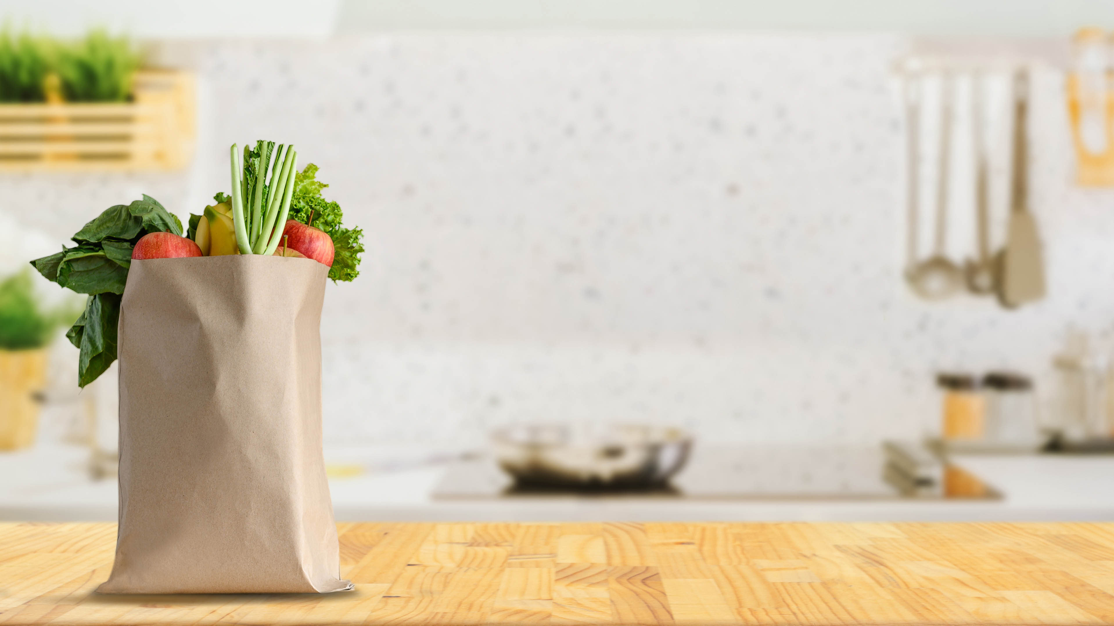 Paper shopping bag full of fruit and vegetable groceries on a kitchen counter