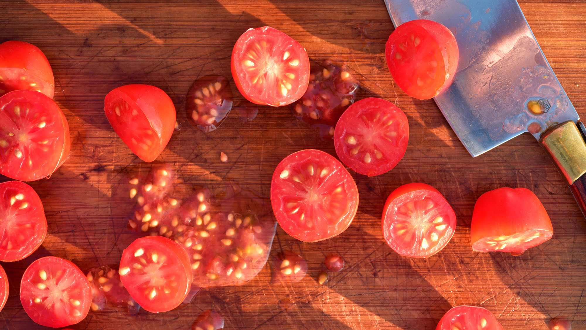 Overhead shot of tomatoes that have been cut in half to show the seeds inside on a cutting board.
