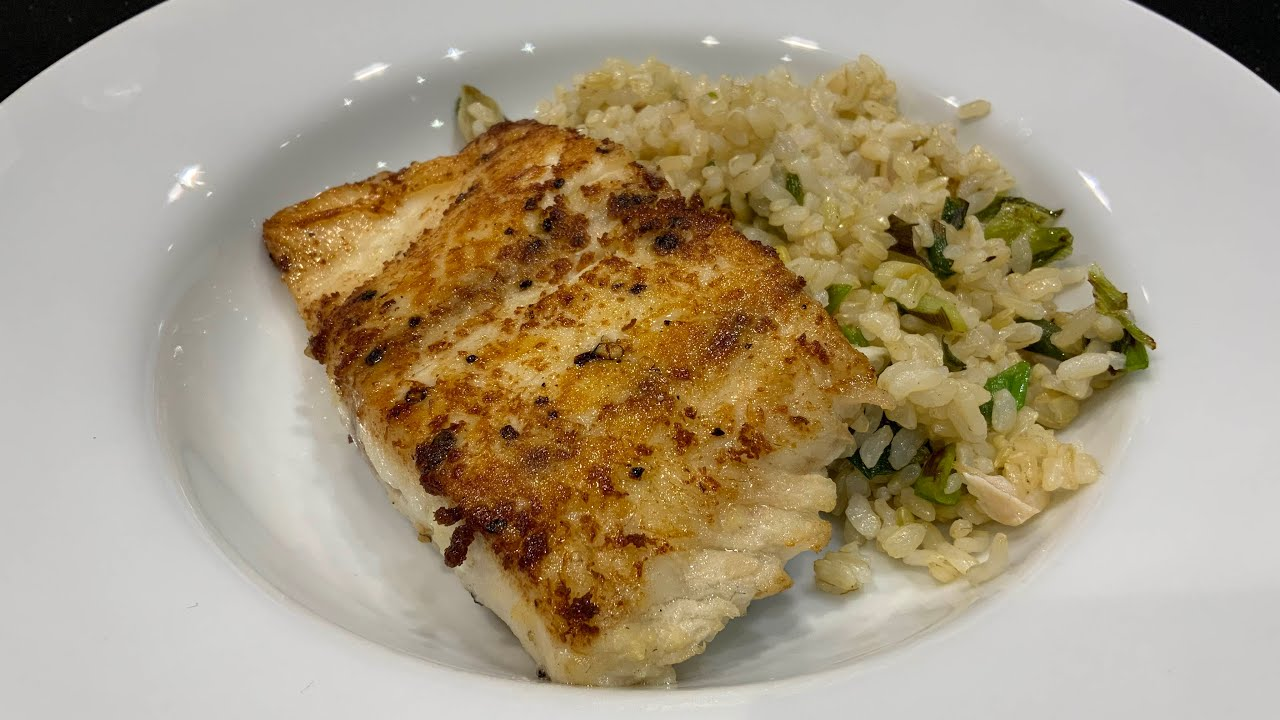 Ginger-crusted bass over vinegar rice displayed on a white dish.