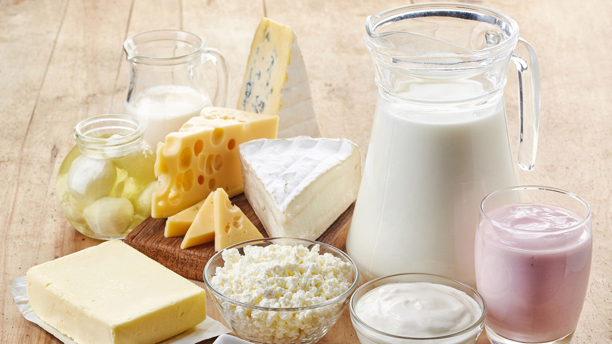 Various fresh dairy products, including a pitcher of milk, cheeses and yogurt, displayed on a wooden countertop.