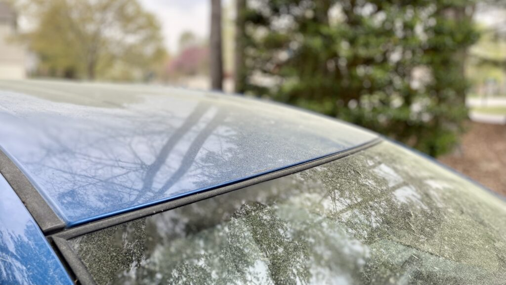 The hood and front window of a blue car is coated with yellow pollen.