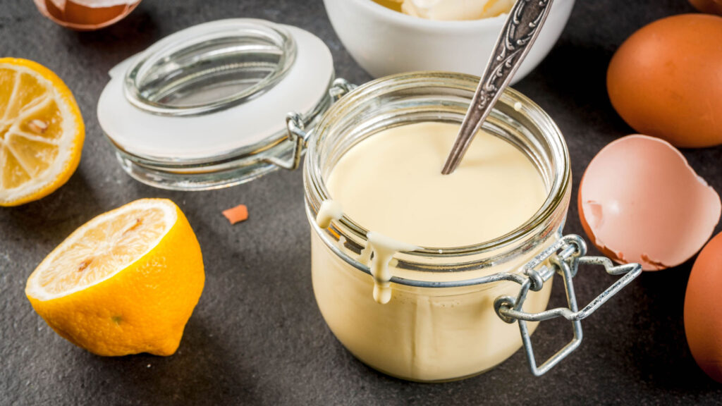 Hollandaise sauce in a glass serving jar, with ingredients like eggs and lemons around the jar on a black stone table.