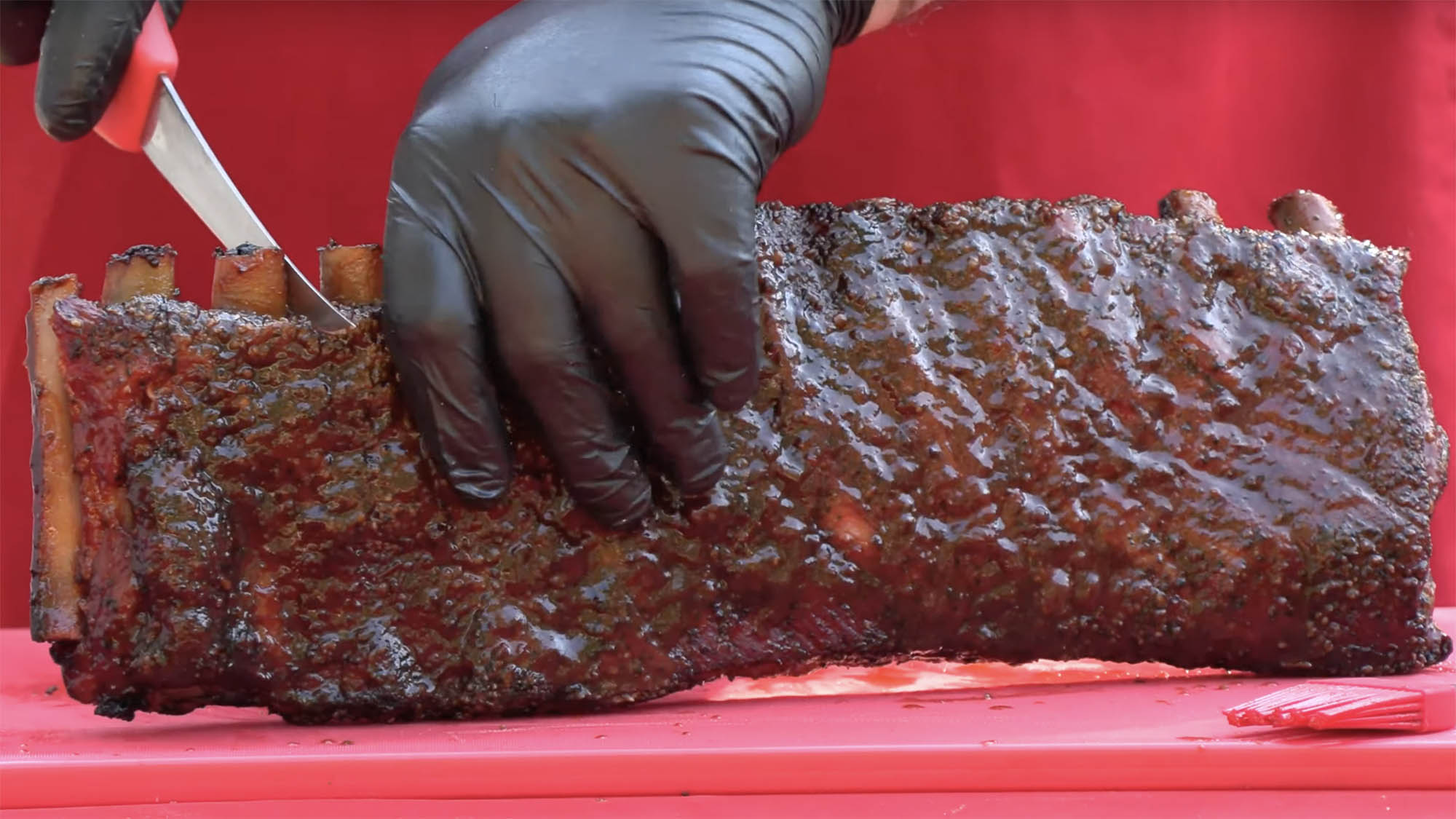 Close shot of gloved hands holding and cutting through barbecue spare ribs on a red tabletop.