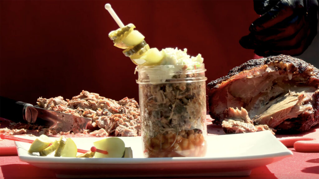 """A glass jar with a """"barbecue martini"""" consisting of pork barbecue, baked beans, cole slaw and pickles sits on a white plate while displayed on a red tabletop outdoors."""