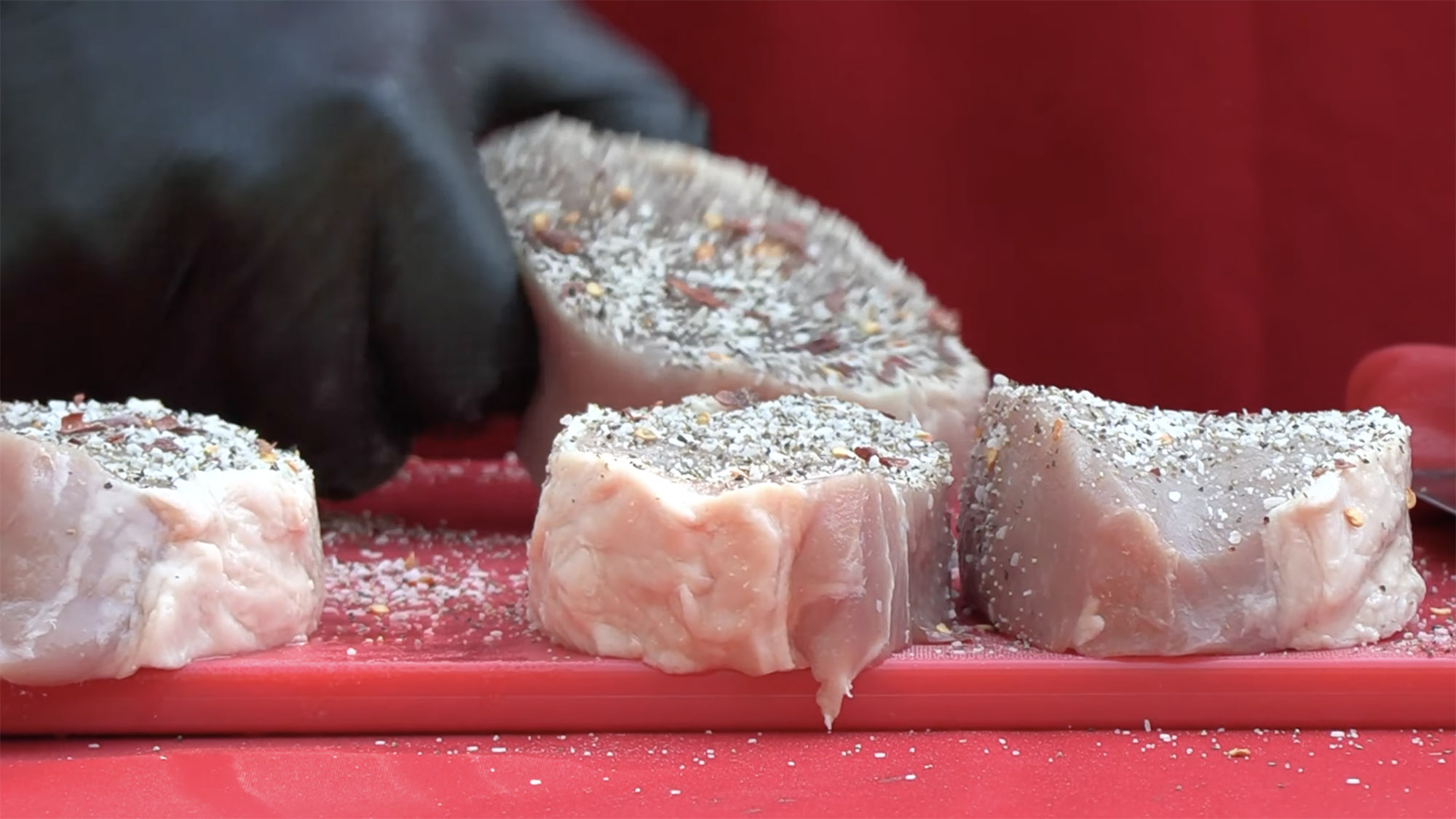 Close shot of raw pork chops on a red tabletop with a dry rub mix sprinkled over them for cooking.