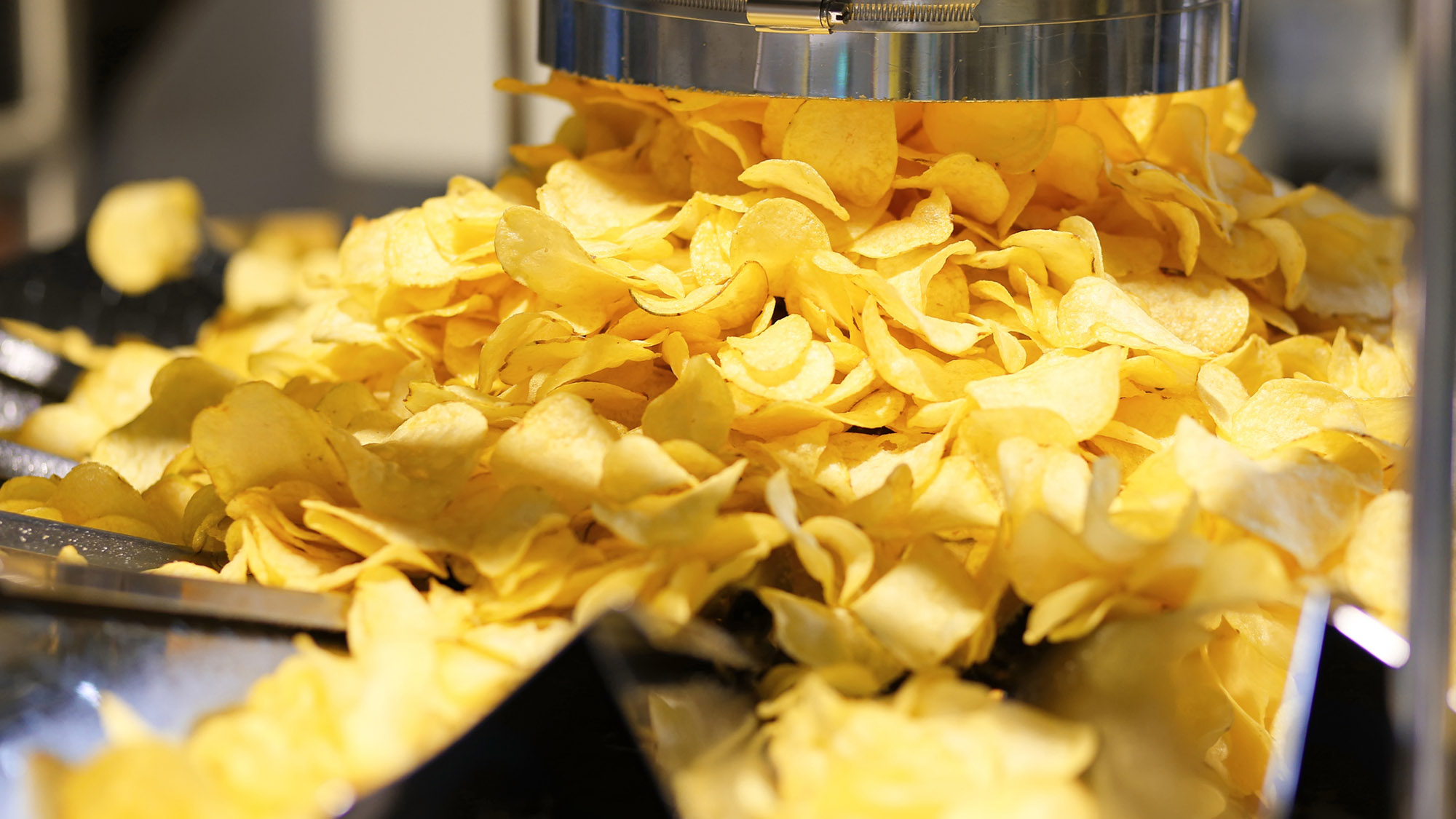 Potato chips production line at the plant. Filling machines for potato chips and snacks.