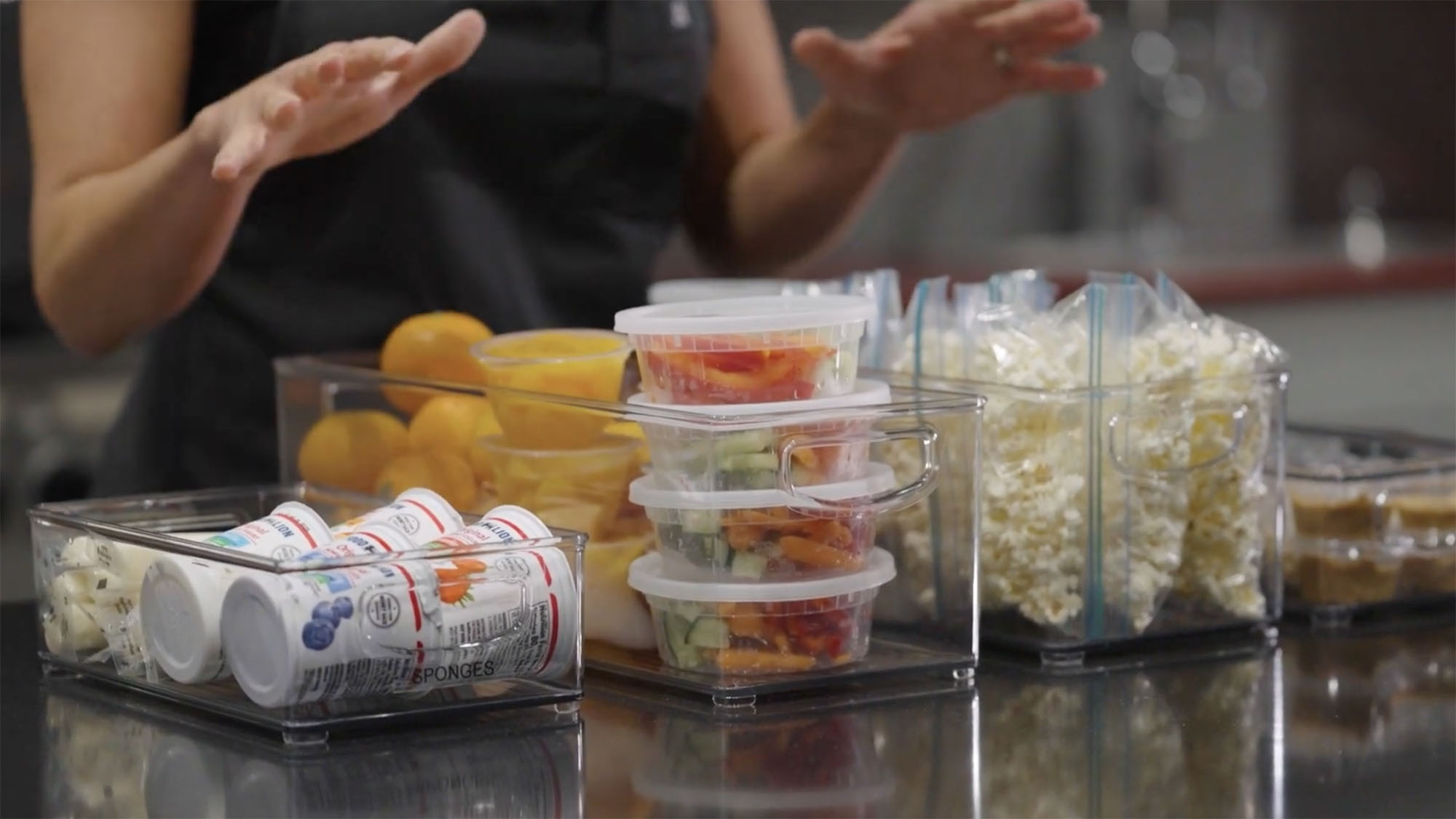 Plastic storage bins are displayed side by side on a kitchen countertop, each of which is filled with various snack items like cheesesticks, yogurt, fruit cups, nuts and other items.