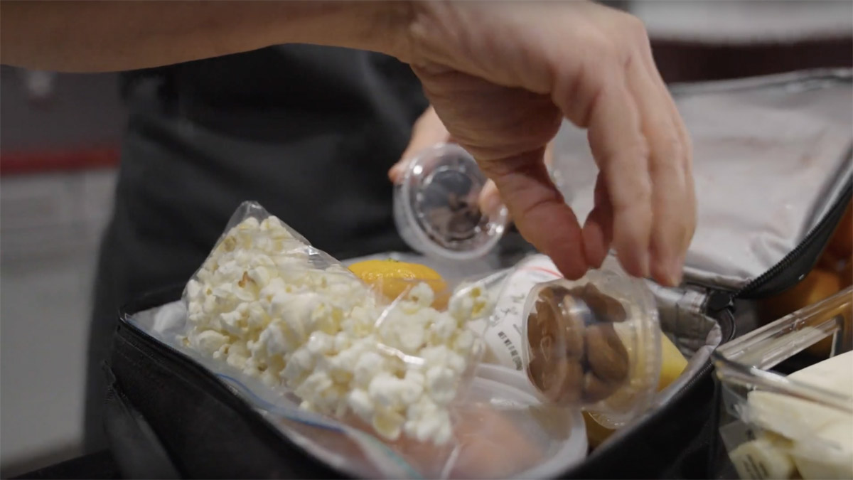 A hand is shown placing healthy snack items, like bagged popcorn, a container of nuts and yogurt, into a child's lunchbag for school.